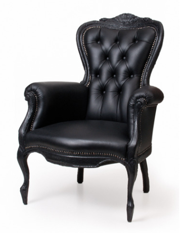 This modern armchair is an ultimate statement silhouette. The Smoke Chair designed by Maarten Baas for Moooi is a strikingly handsome, baroque style armchair with a fiery past. The wood frame, legs, and arms were charred in the manufacturing process to capture the look of a burned antique, that's ever-resilient in its modern form.