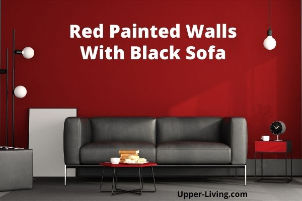 Red painted wall with black living room furniture.