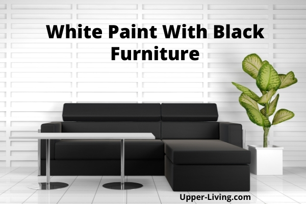 White painted wall with black living room furniture.